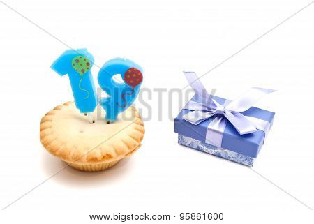 Cupcake With Nineteen Years Birthday Candle And Gift On White