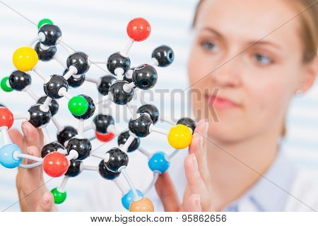 Technician in chemical laboratory with model of molecule