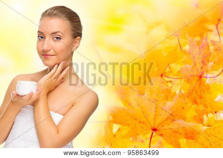 Young healthy woman with body cream on autumnal background