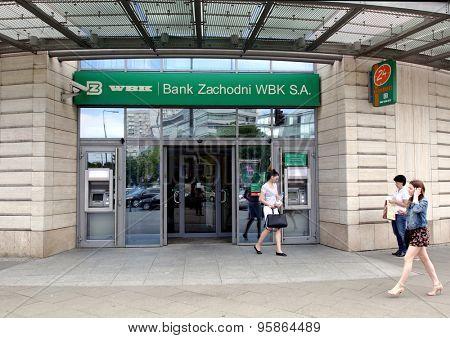 WARSAW, POLAND - SATURDAY, JUNE 6, 2015: Pedestrians walk past a Bank Zachodni WBK branch. Bank Zachodni WBK (BZ WBK) is the third largest bank in Poland