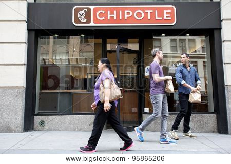 NEW YORK CITY - FRIDAY, JUNE 19, 2015: Pedestrians walk past a Chipotle fast food restaurant. Chipotle Mexican Grill, Inc. is a chain of restaurants