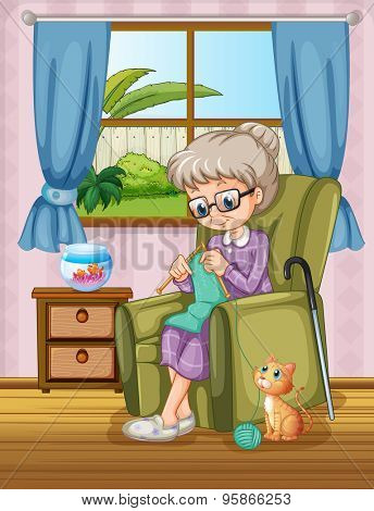 Old woman sitting on a sofa knitting with a cat sitting nearby