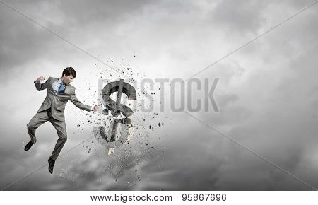 Businessman breaking stone dollar symbol with karate punch