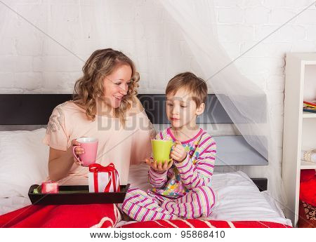 Nice woman and little boy having breakfast
