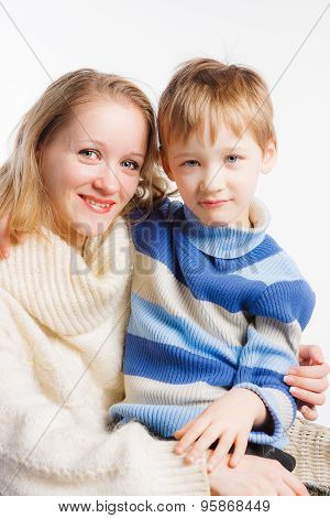 Beautiful woman sitting on chair with her little son on her lap