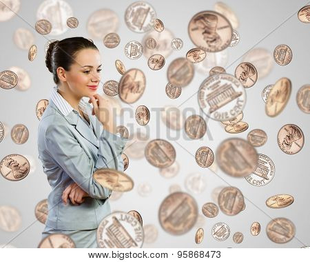 Image of thoughtful businesswoman standing under coin rain