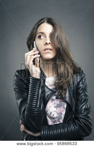 Attractive Young Girl At Phone Looking Aside On Texture Background