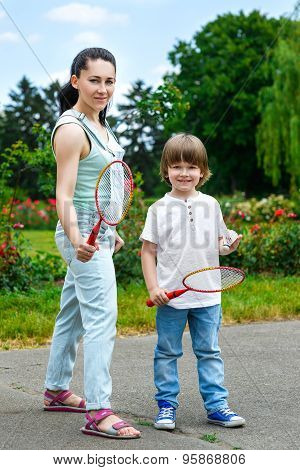 Portrait of small boy in park holding a racquet for badminton smiling, and his happy mother standing