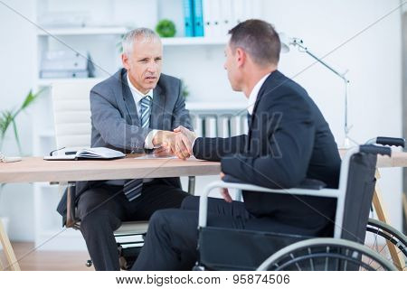 Businessman in wheelchair shaking hands with colleague in the office