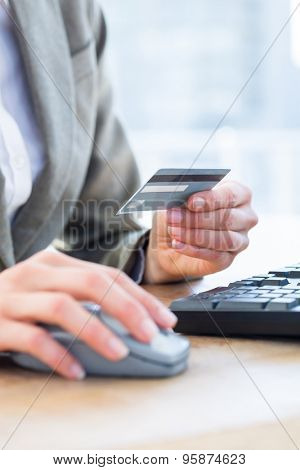 Businessman pay with her credit card on internet at the office
