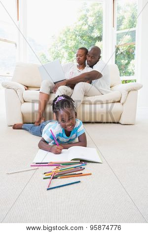Pretty couple using laptop on couch and their daughter drawing in living room