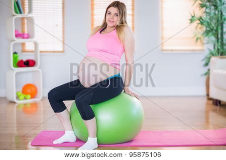 Pregnant woman looking at camera sitting on exercise ball in the living room