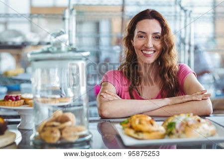 Pretty brunette smiling at camera behind counter at the bakery