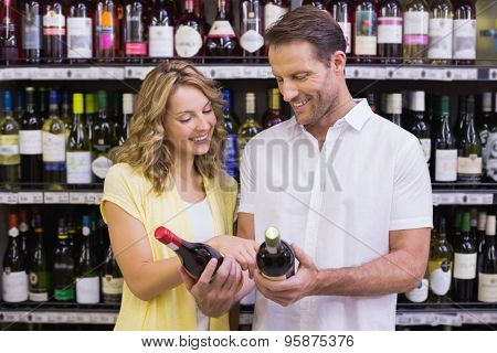Smiling casual couple looking ar wine bottle in supermarket
