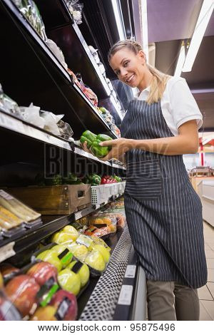 Pretty blonde holding peppers in the supermarket