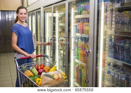 Pretty woman looking at camera and taking product on fridge at supermarket
