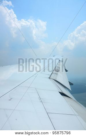Wing of airplane flying above clouds with nice sky