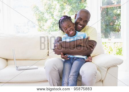 Happy smiling father to hug with her daughter in couch in living room