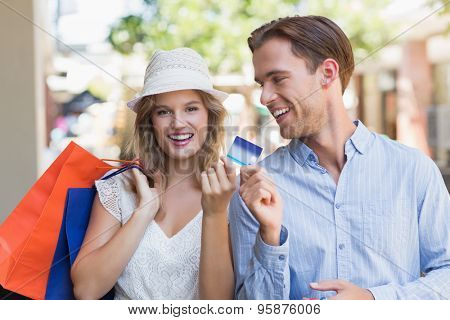 Portrait of a cute couple handing a credit card