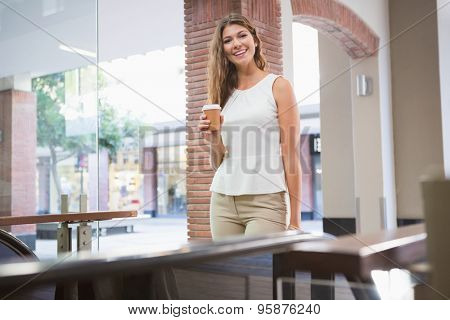 Portrait of smiling woman with coffee to go looking at camera at the shopping mall