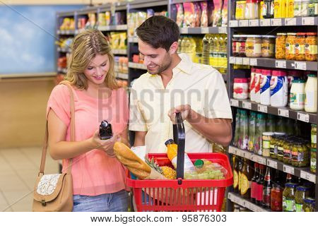 Smiling bright couple buying food products with shopping basket at supermarket