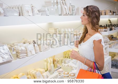 Smiling woman browsing products at a beauty salon