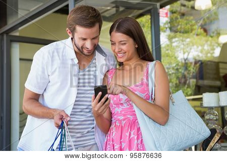 Happy couple smiling and looking at mobile phone after shopping