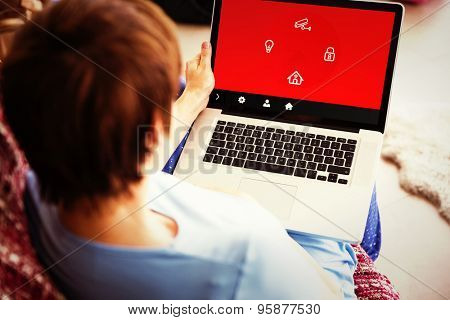 Pregnant woman using her laptop against home automation system