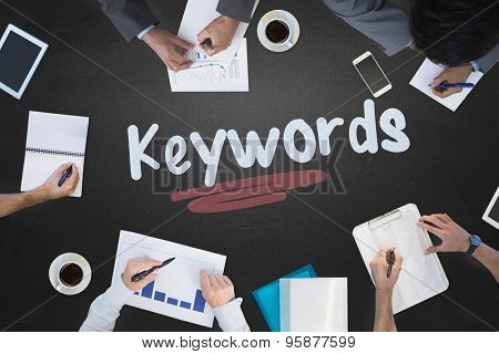 The word keywords and business meeting against blackboard