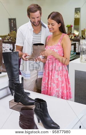 Happy couple smiling at a shoe in a shoe store