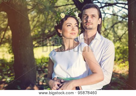 wedding couple, beautiful young bride and groom standing in a park outdoors holding hands