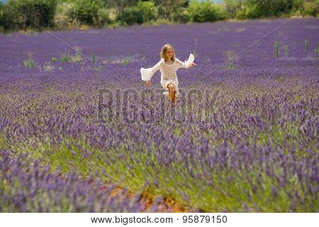 Beautiful blonde girl jumps in lavender field
