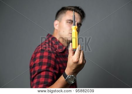 Young man holding a screwdriver over gray background