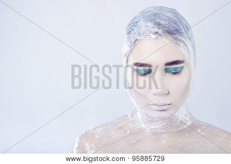 Misterous pretty woman wrapped in cellophane looking forward standing on light grey background
