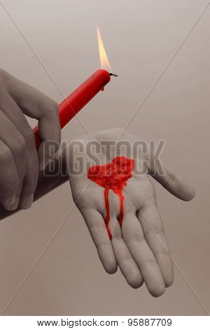 Special Toned Photo Of Female Hands Holding Red Wax Candle Dripping On A Palm