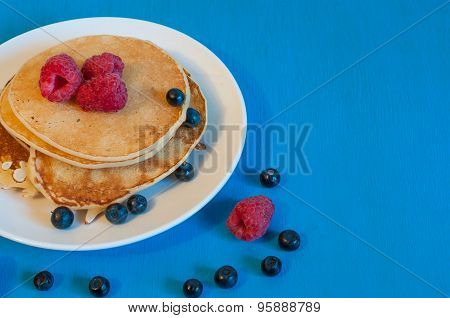 Stack of wheat golden pancakes or pancake cake with freshly picked raspberry on a dessert plate. Top