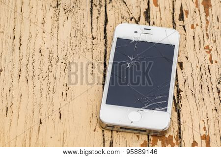 Smartphone with badly broken screen against rusty wooden background