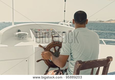 Captain Of A Yacht Sitting By The Steering Wheel