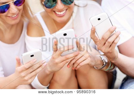A picture of a group of friends using smart phones in the city