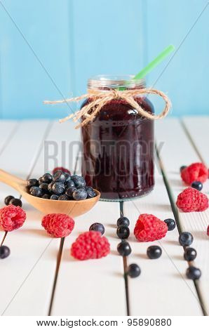 Bilberries in wood spoon. Crimson raspberry and jar of bilberry jam jn light wooden background. Sele