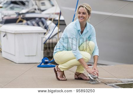 A blonde model posing outdoors with boats