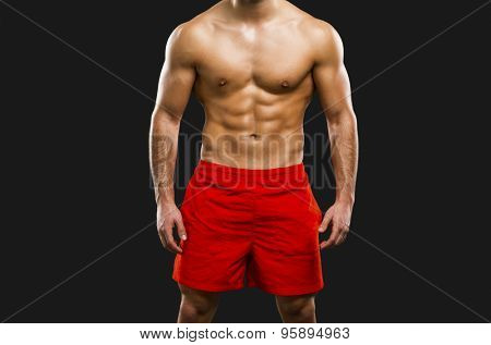 Handsome and sexy muscular man, isolated over gray background
