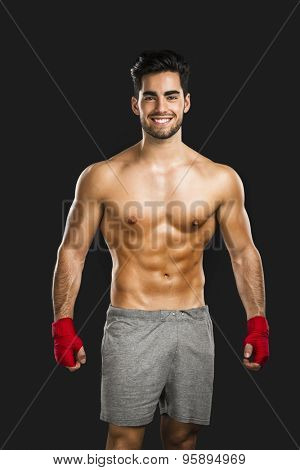 Portrait of a young male Body Combat atlhlete, isolated over a gray background