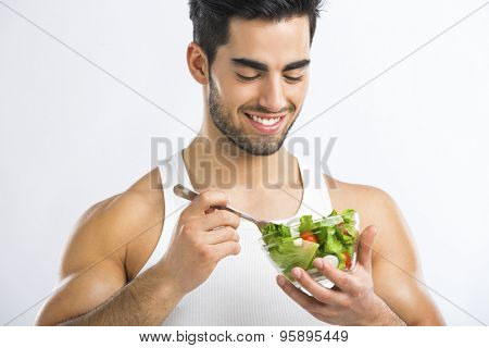 Handsome young man eating a healthy salad, isolated over a gray background
