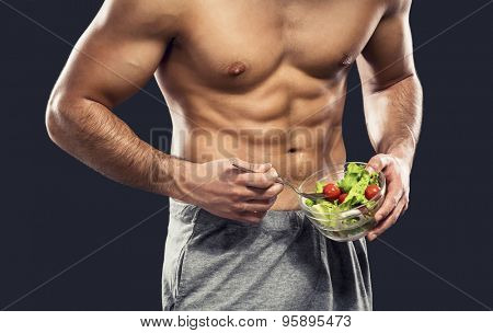 Muscular man eating a healthy salad, isolated over a gray background