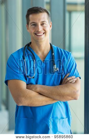 cheerful young medical intern standing in hospital