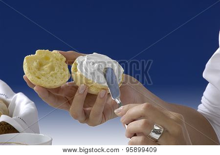 hands passing cream cheese  on a blue background