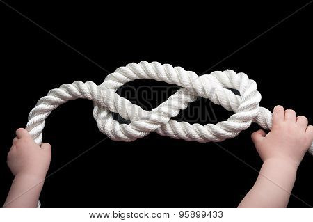 Baby hands holding overhand knot