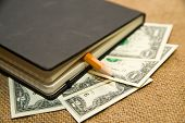 stock photo of memento  - notebook with a blank sheet pencil and money on the old tissue - JPG