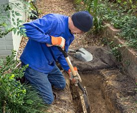 pic of pipe-welding  - Man digging trench to replace old sewer pipes and lawn sprinkler system line - JPG